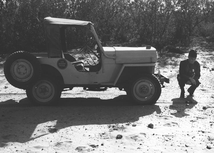 Border Patrol Inspector observing sign of possible illegal border crossers encountered while on Jeep patrol duty near Del Rio, Texas - March 9, 1956.