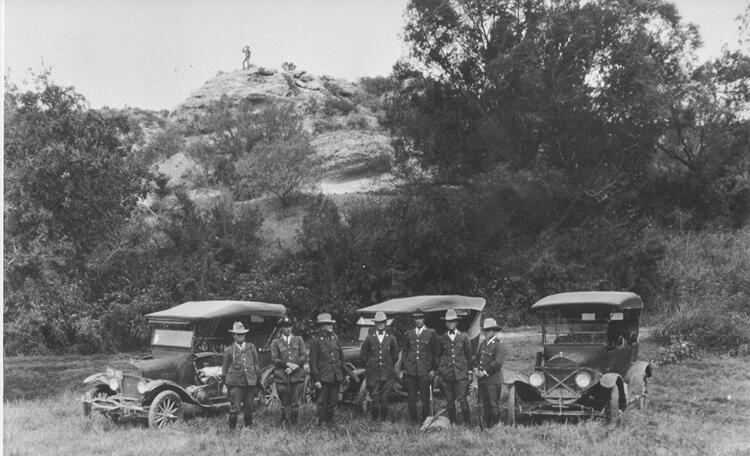 Patrol Inspectors gathered near Del Rio, Texas in 1925. Inspectors include (left to right) Homer E. Watkins, F. L. Centilli, Tom Hulsey, Wesley Stiles, D.L. Kight, Loy C. Henry, and Quincy Binum. On the hill is Patrol Inspector Paul White.