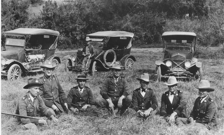 Del Rio Border Patrol Inspectors gathered near vehicles in 1925. Patrol Inspectors include (left to right) F.L. Centilli, Tom Hulsey, D.F. Kight, Homer E. Watkins, Loy C. Henry, Wesley Stiles, and Quincy Binum. Standing near vehicles is Patrol Inspector Paul White.