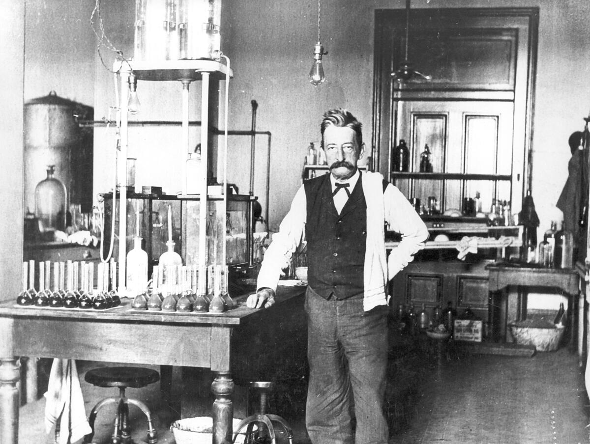 Chief Chemist Walter L. Howell analyzing sugar at the New Orleans laboratory, 1906. The flasks on the left contained sugar in solution, while the ones on the right incorporated a small amount of lead acetate to determine impurities.