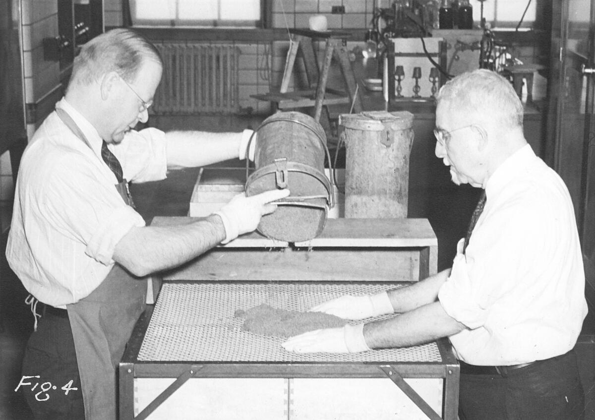 Philadelphia laboratory, circa 1948. Chief Chemist William C. Beard on the left, and Charles Curtis on the right, are shown dividing raw sugar for sampling.