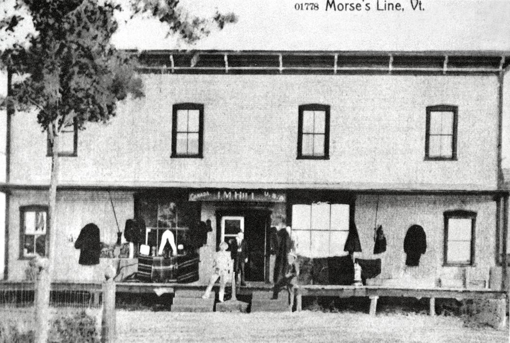"The second J. Morse line store when under the proprietorship of J.M. Hill, Jr. The store, which gave the hamlet the name Morses Line, straddled the international boundary. Boundary marker no. 621 is positioned in-between the two sets of steps, while the store sign overhead indicates the ""Canada"" side and ""U. S. A."" side of the building. This postcard view is from ""A History of Franklin, 1789-1989,"" p.108 (photograph provided by Wilfred Rainville, of Morses Line.)"
