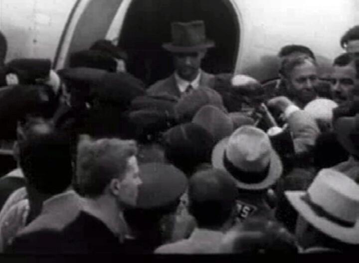 Howard Hughes in the doorway of his plane, surrounded by press and well-wishers, shortly after setting the round-the-world record.