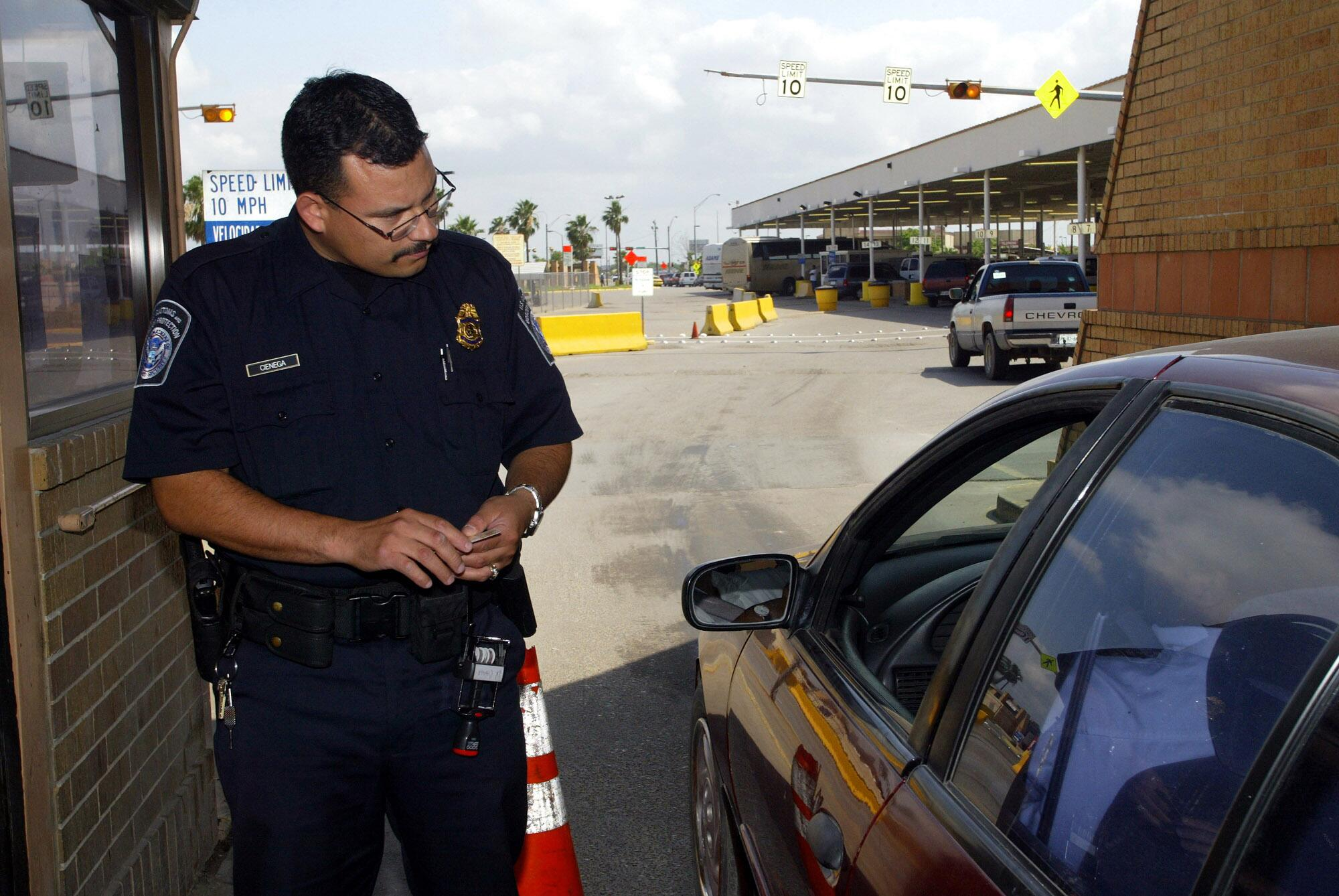 A CBP officer speaks with individuals as they enter the United States.