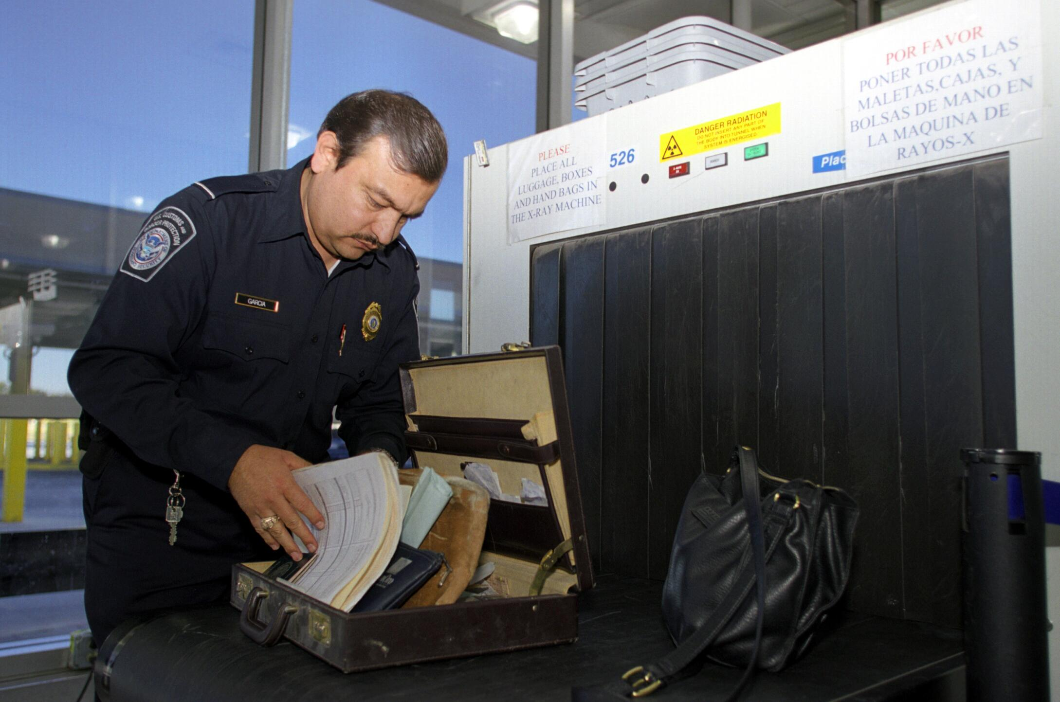 A CBP officer checks an individual's luggage after being x-rayed.