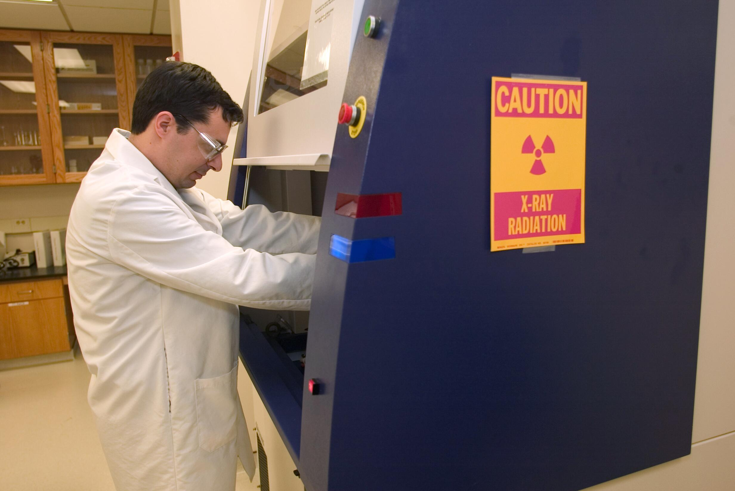 CBP Laboratory personnel remove items from x-ray testing equipment.
