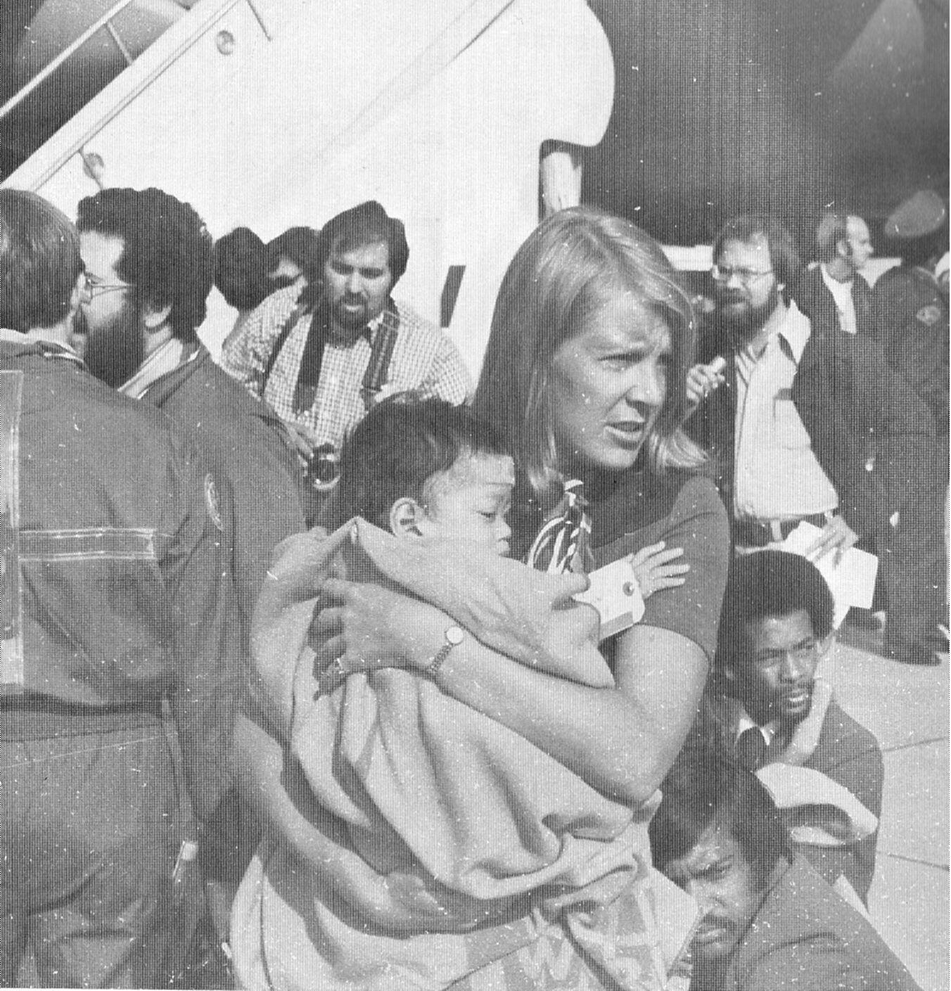 Denise Crawford of the U.S. Customs Service holds a Vietnamese refugee. Between April 26 and May 30, 1975, military customs inspectors-under the supervision of U.S. Customs advisors-processed more than 60,000 U.S.-bound Vietnamese refugees at Guam and Subic Bay, the Philippines. (Update '75, U.S. Treasury)