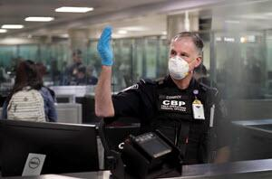 An officer with U.S. Customs and Border Protection gestures for arriving international travelers to proceed forward through the line at Dulles International Airport near Washington, D.C