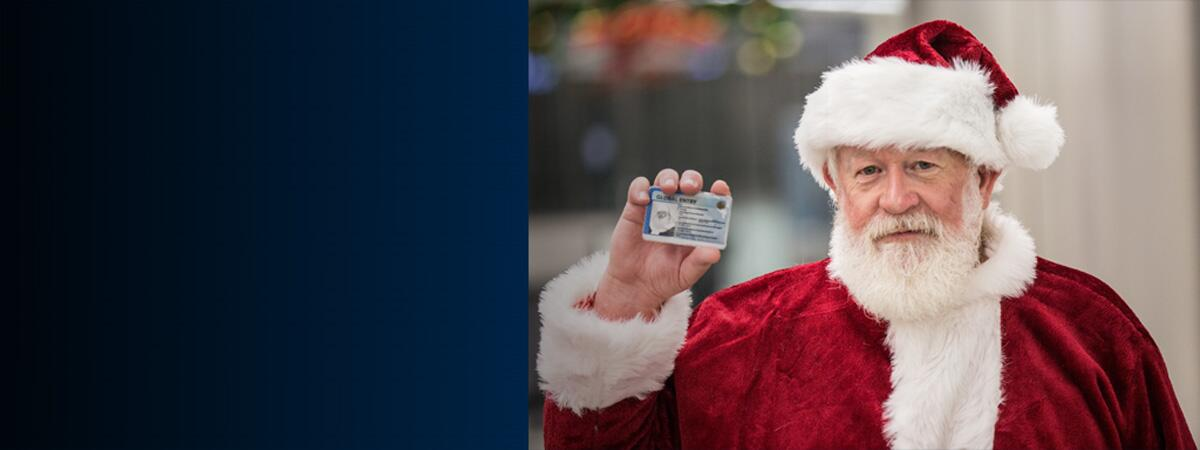 Santa holding his Global Entry card