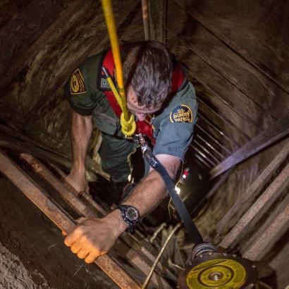 Photo of Border Patrol agent descending into tunnel
