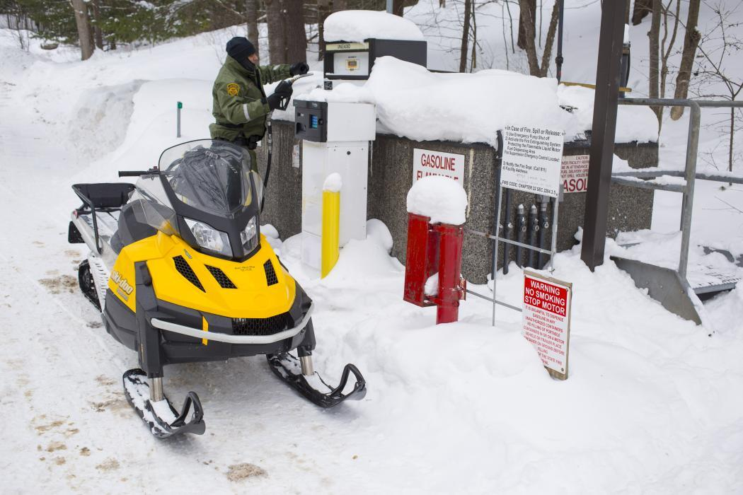 Photo of Border Patrol agent filling his snowmobile with gasoline.