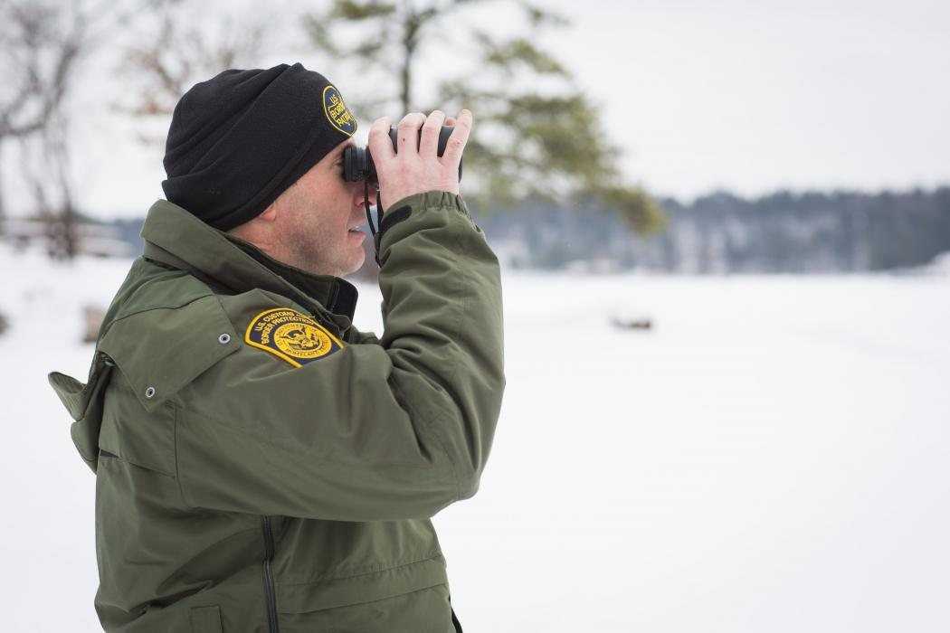 Photo of a Border Patrol agent using binoculars in surveillance along the St. Lawrence River