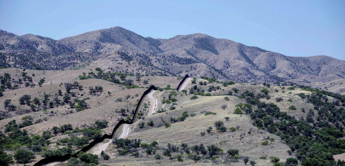 Photo of surveillance technology and a border fence in Arizona