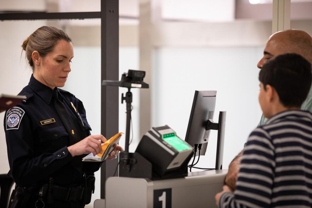 A CBP officer screens a man and boy at the Jacksonville, Florida, international airport