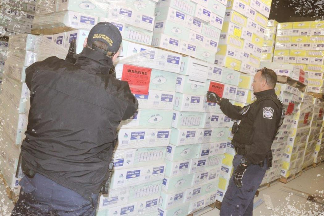 CBP Office of Field Operations Seized Property Specialists Gary Dziatko (left) and Michael Morejon inspect boxes of frozen squid