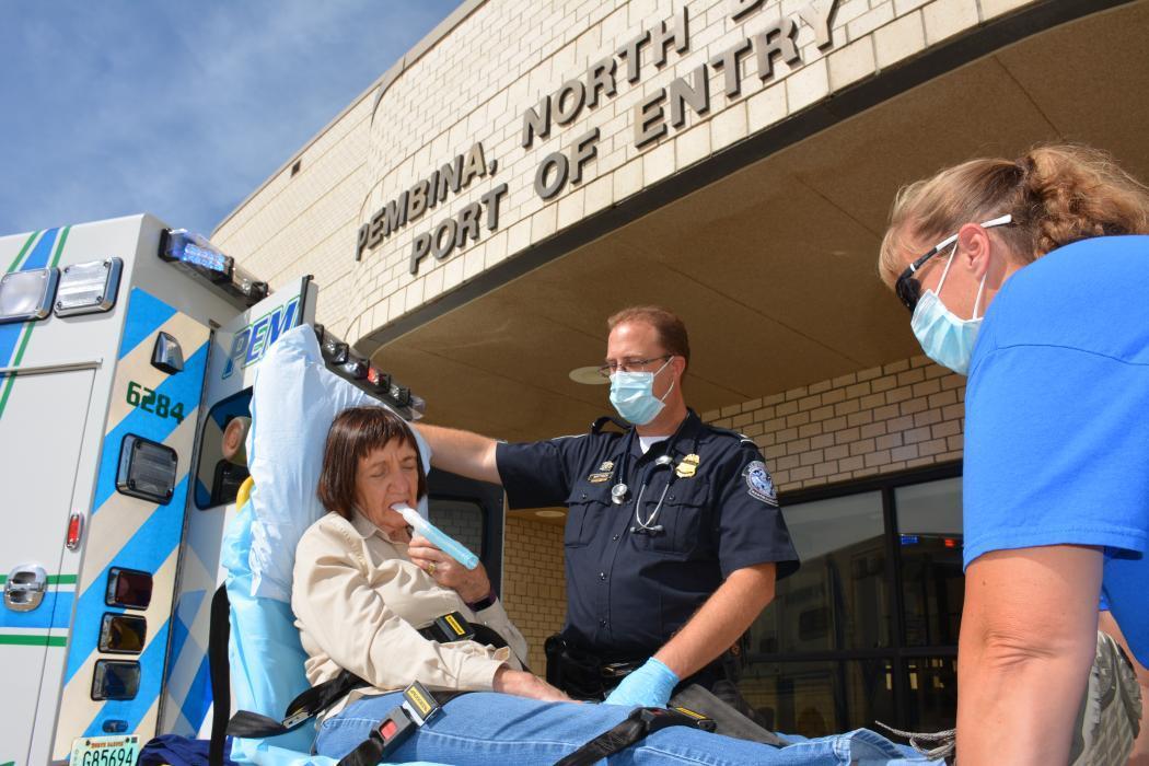 CBP Officer Jeremy Mattison helps a patient at port of Pembina, North Dakota