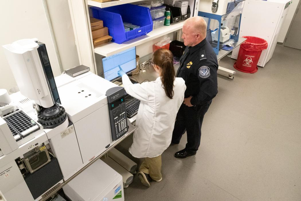 CBP scientist and CBP officer work in a lab