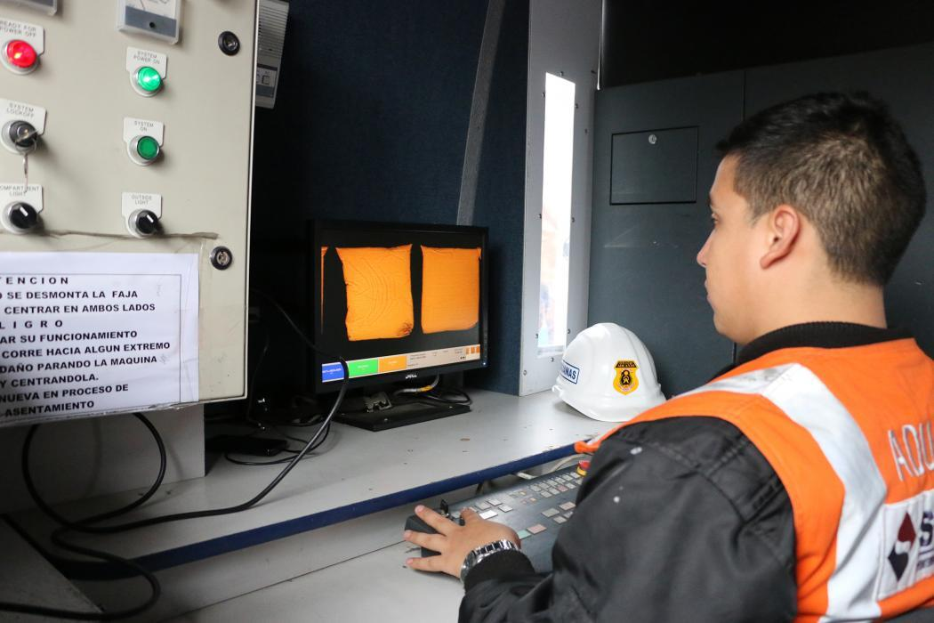 Photo of a Peruvian Customs officer examining bags of quinoa using an X-ray screening system in Calleo, Peru.