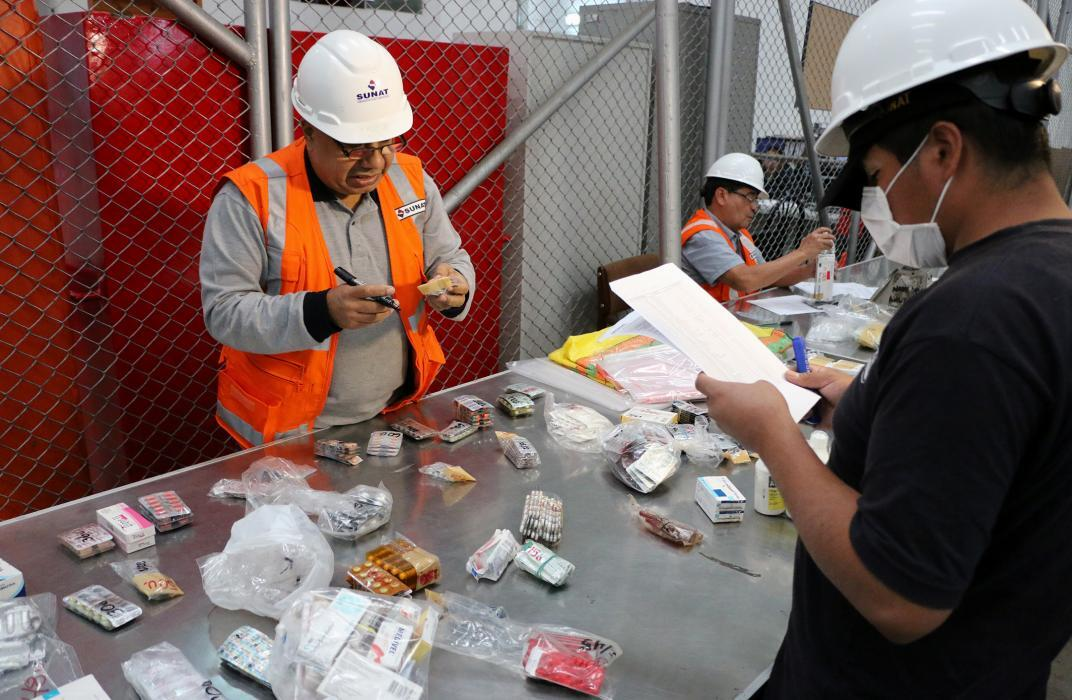 Photo of Peruvian customs inspectors processing illegal pharmaceuticals at storage warehouse
