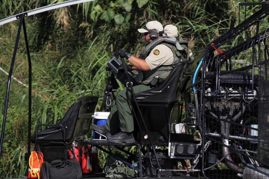 Photo of a riverine agent exploring signs of activity on the Rio Grande
