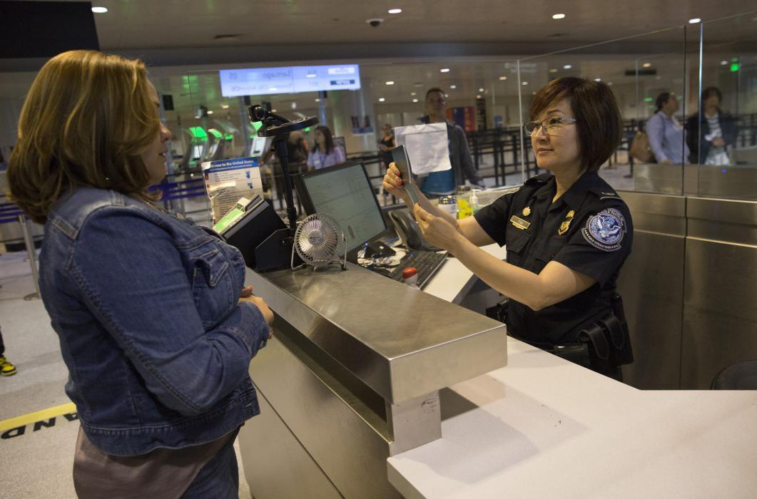 A CBP officer processes an international passenger at Boston Logan International Airport.