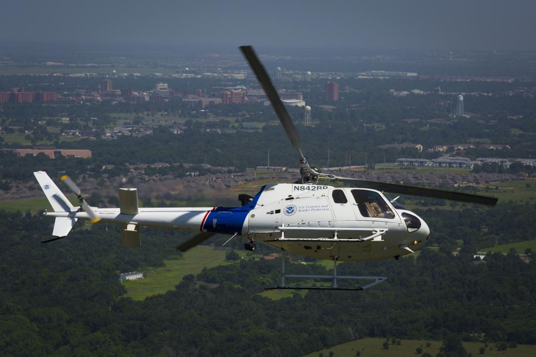 Photo of a CBP helicopter making a steep turn in the skies above Oklahoma City.