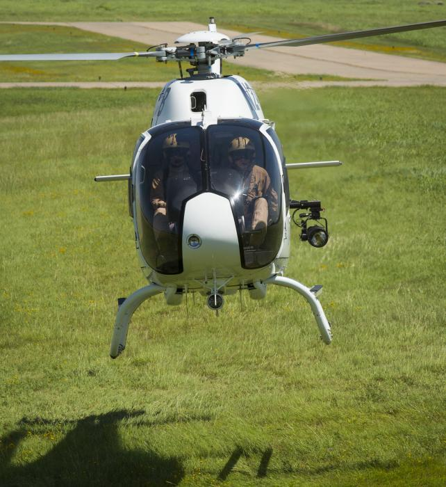 Photo of CBP pilots practicing hovering over grass.