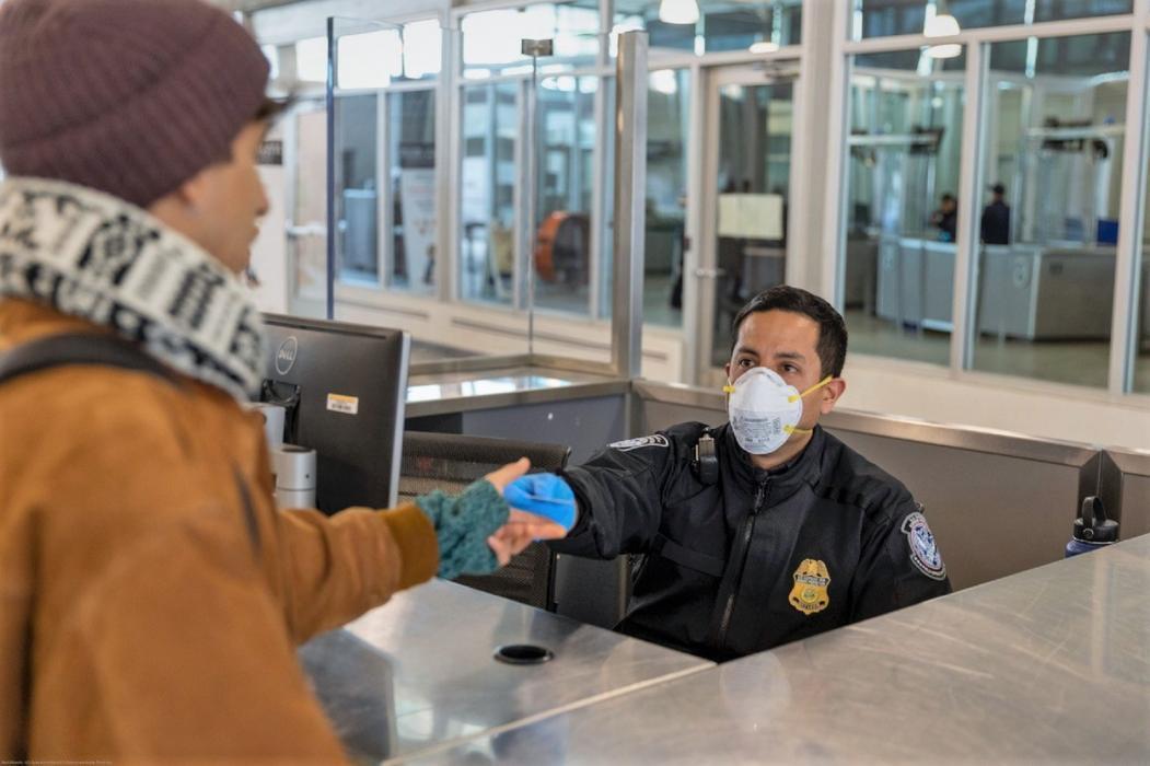A CBP officer talks with a traveler