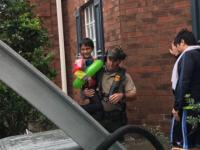 Border Patrol Agent Robert Gardner carrying child to waiting boat.