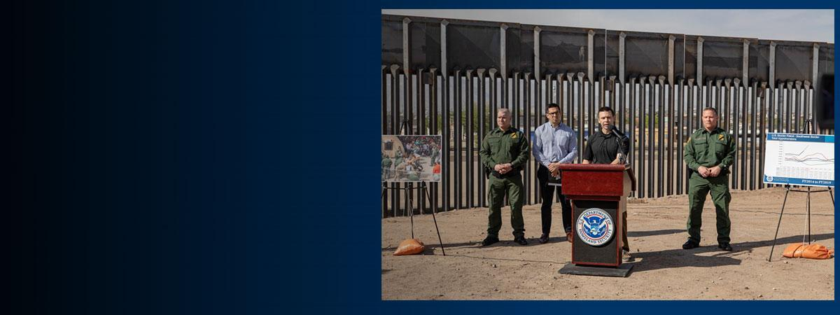 Commissioner McAleenan stands in front of the Border Wall
