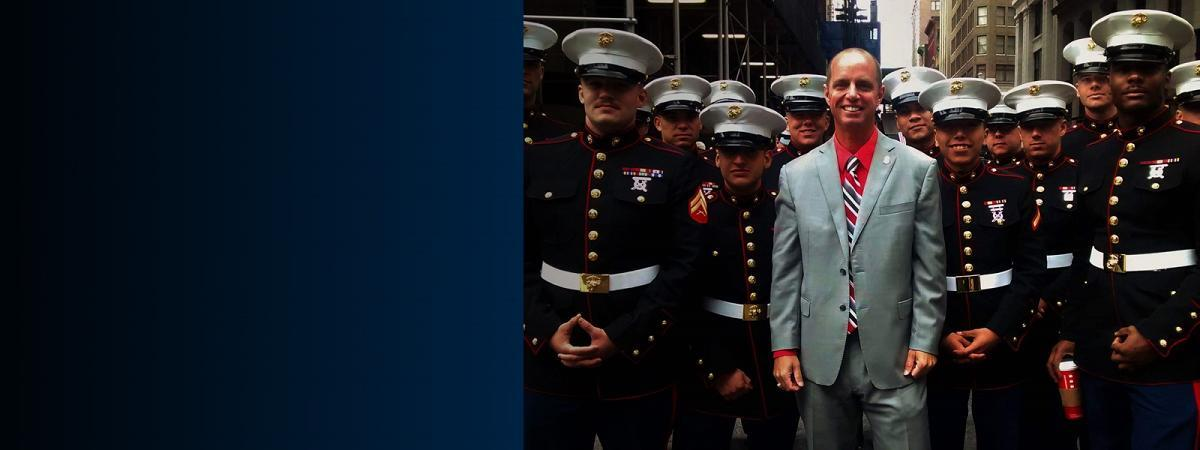 Jeffrey R. Jack, Veterans Employment Program Manager standing with United States Marines in uniform at the Veteran's Day parade