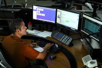 Photo of man looking at computer screens