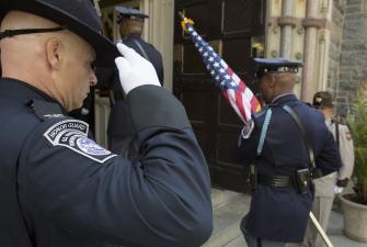 CBP honor guard member salutes flag.