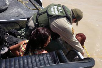 Border Patrol resuces two from river.