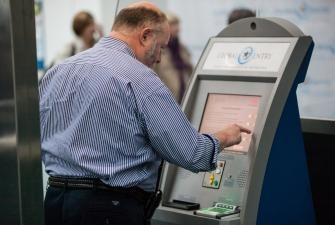 An arriving passenger uses a Global Entry kiosk.