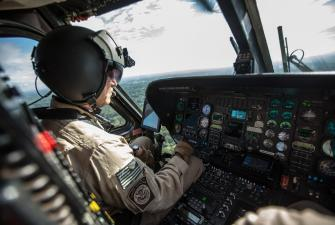 A CBP Air Interdiction Agent patrols in a Black Hawk helicopter.