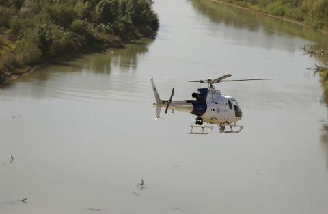 An Air and Marine Operations AS350 crew flies over the Rio Grande River during a border security patrol near McAllen, Texas.
