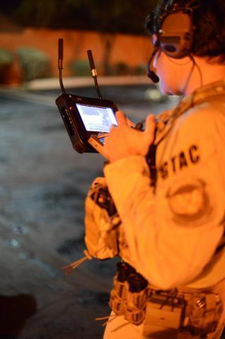 An AMO Ground Team Air Coordinator preparing for the execution of numerous search and arrest warrants in southern Arizona that dismantled a local drug trafficking organization suspected of distributing and selling heroin, marijuana, and various firearms.