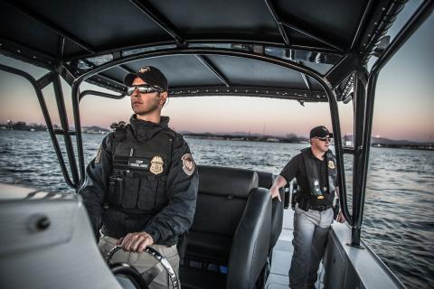 An Air and Marine Operations Marine Interdiction Agent conducts a maritime patrol while another crew member keeps and eye out for suspicious activity near San Diego, California.