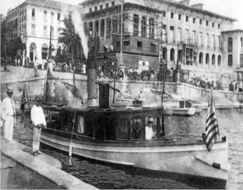 Customs cutter leaves the dock at the U.S. Custom House in San Juan, Puerto Rico. In the background is the U.S. Post Office then under construction.
