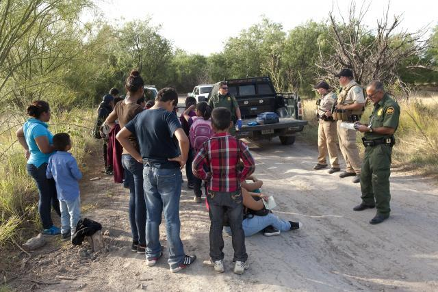 Border Patrol agents begin to process a group of migrants apprehended near the border. Agents learn basic Spanish as part of their training.