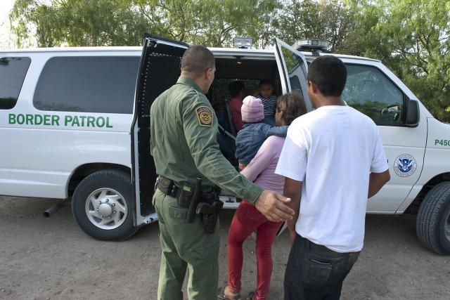 Border Patrol agents load a young family into a transport van to take them t