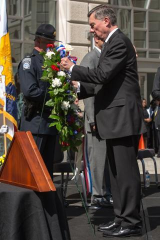At the May 2014 CBP Valor Memorial ceremony, Commissioner Kerlikowske places a flower in a wreath to honor CBP's fallen employees. CBP Acting Deputy Commissioner Kevin McAleenan stands at right.
