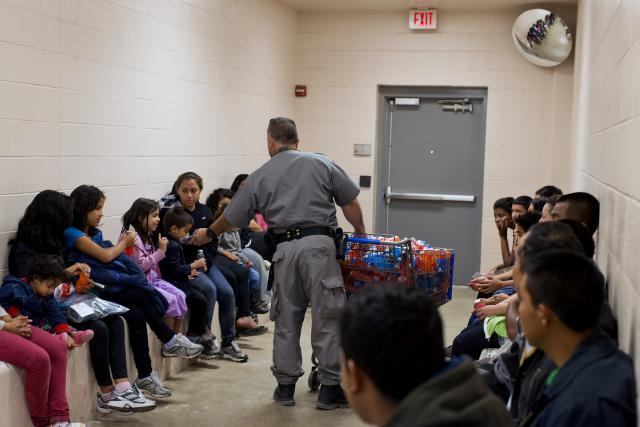 An officer distributes juice at McAllen, Texas Border Patrol facility. <em>(Photo by Hector Silva)</em>