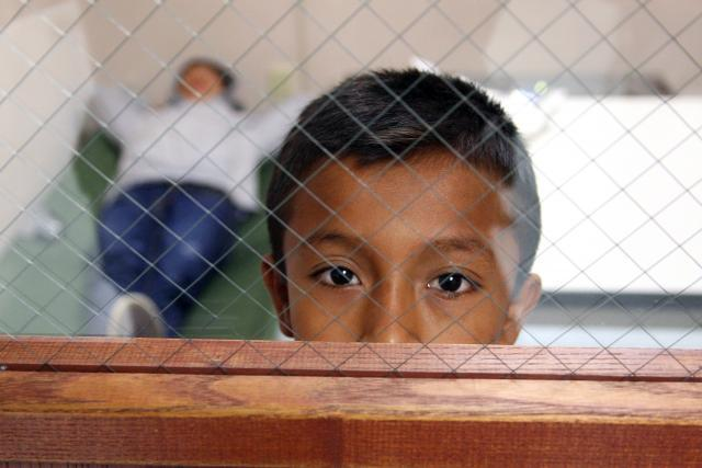 A youngster looks out the door window from the room he is staying in at the Brownsville, Texas port of entry. <em>(Photo by Eduardo Perez)&lt