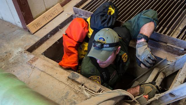 A Border Patrol agent descends into the tunnel.