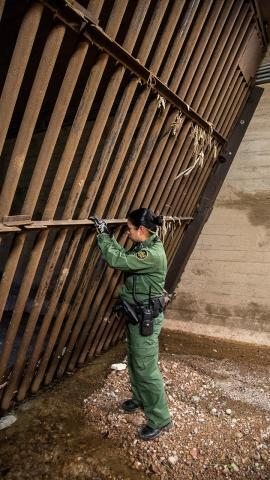 A Border Patrol agent looks through the steel gates in Nogales' main drainage system, which were built to prevent drug and human trafficking.