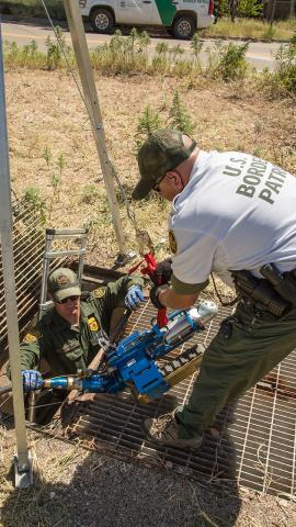 Border Patrol agents remove the robot from the drainage pipe after it completes the task.
