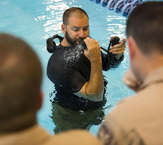 Instructor Chad Warren shows agents how to clear the mouthpiece of an air bottle while they're underwater.