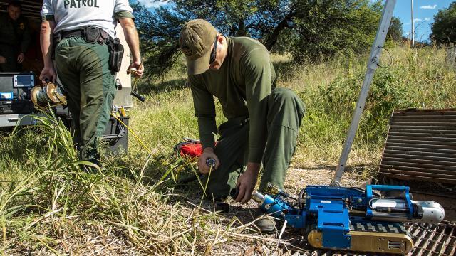A Border Patrol agent prepares a CBP robot before it explores a drainage tunnel.